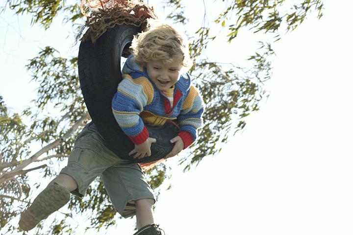 Boy swinging fast on a tire swing on a farm.